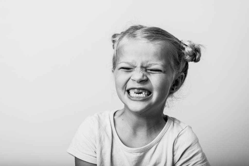 7 Year old first grade girl laughing in a fine art school portrait