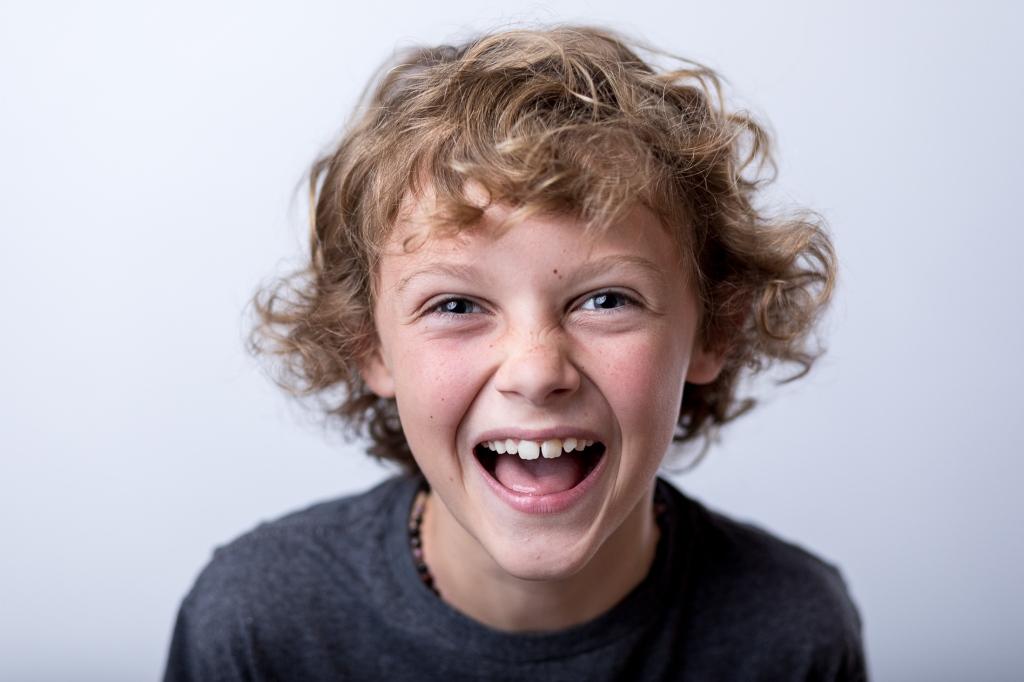 9 Year old, 4th grade boy laughing in a fine art school portrait.